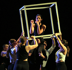 dancers on stage carrying a cube prop