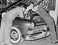 Historical photo of SRJC students fixing a car