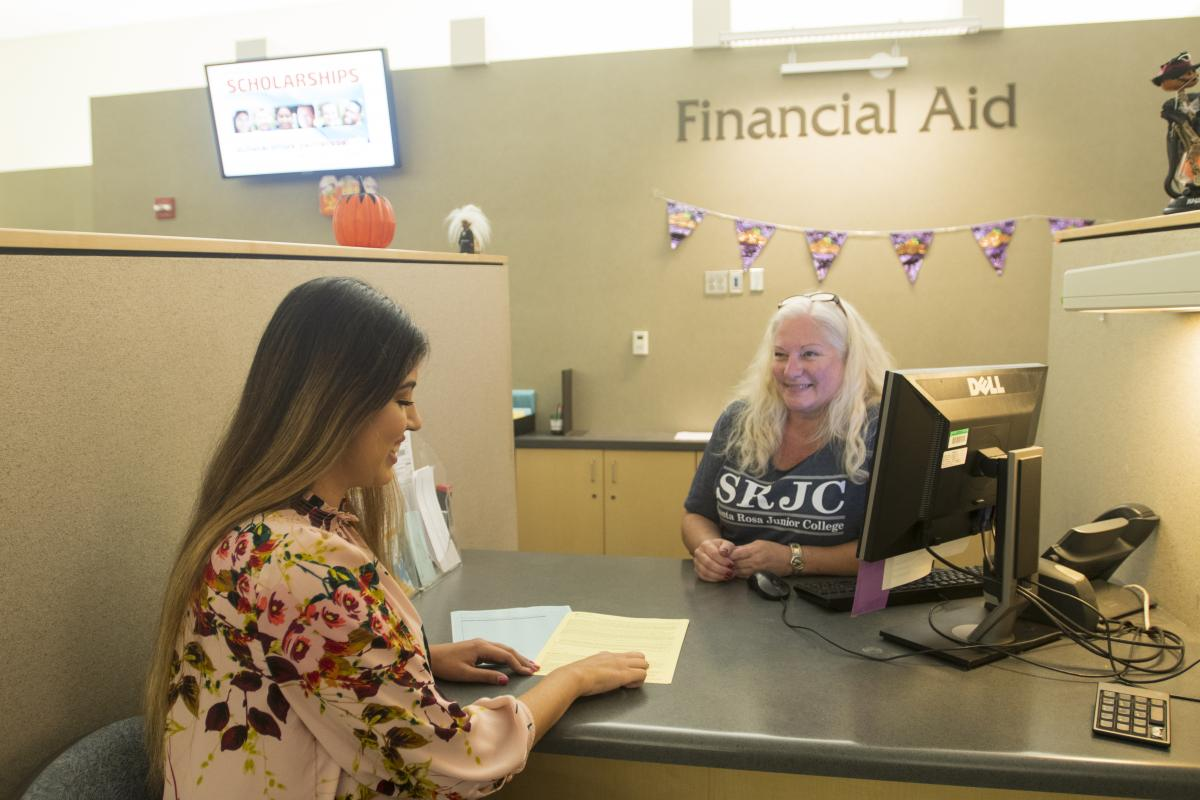 student and financial aid employee talk over a desk